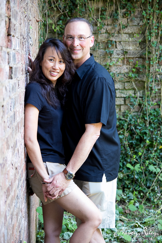 Engagement couple against ivy and brick