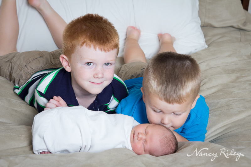 newborn with brothers on bed